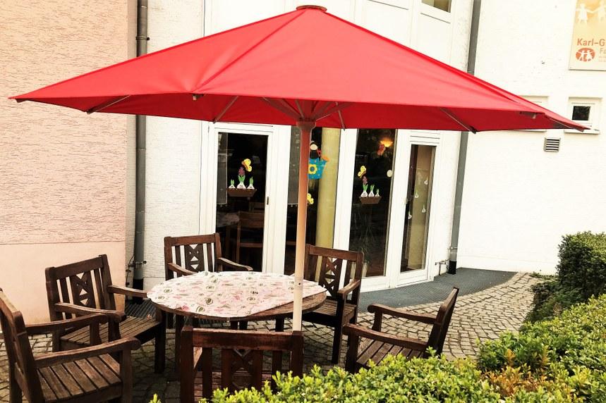 Roter Sonnenschirm auf Terrasse